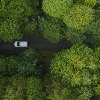 aerial view of delivery truck driving through a forest road